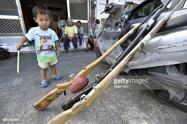Tama Talum's son an aboriginal hunter stands next to the shot guns in front of his home in Taitung eastern Taiwan on July 2 2016 New president Tsai...