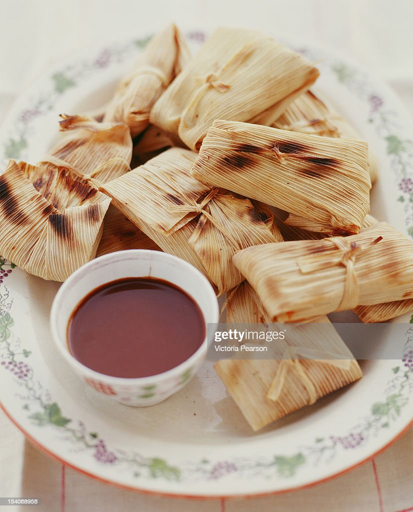 Tamales with red mole sauce.