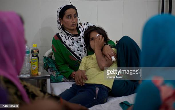 Tamanna whose eye was damaged after Indian government forces fired pellets towards her rests in the lap of her mother at a hospital on July 11 2016...