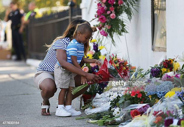 Tamara Holmes and her son Trenton Holmes lay flowers in front of Emanuel AME Church after a mass shooting at the church that killed nine people of...