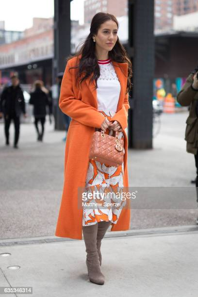 Tamara Kalinic is seen attending Tory Burch during New York Fashion Week wearing an orange coat with white and orange bird skirt on February 14 2017...