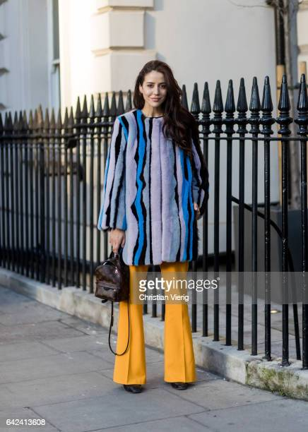 Tamara Kalinic wearing a striped coat mustard flared pants Louis Vuitton backpack outside Daks on day 1 of the London Fashion Week February 2017...