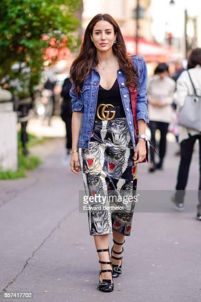 Tamara Kalinic wears a blue denim jacket a Dior bag a Gucci belt a print skirt outside Moncler during Paris Fashion Week Womenswear Spring/Summer...