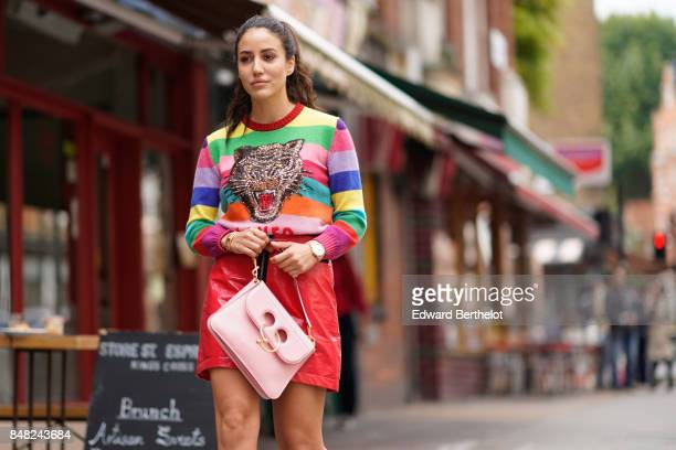 Tamara Kalinic wears a colored striped top with a tiger print a red skirt a pink bag outside JW Anderson during London Fashion Week September 2017 on...