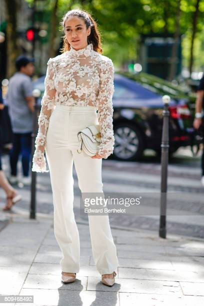 Tamara Kalinic wears a white lace top white flared pants white shoes outside the Zuhair Murad show during Paris Fashion Week Haute Couture...