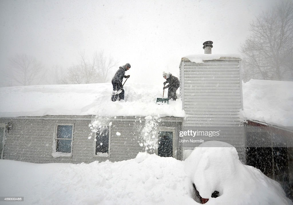 Tami Normile and Richard Brooks attempt to remove some of the five feet of snow from a roof top on November 20 2014 in the Lakeview neighborhood of...