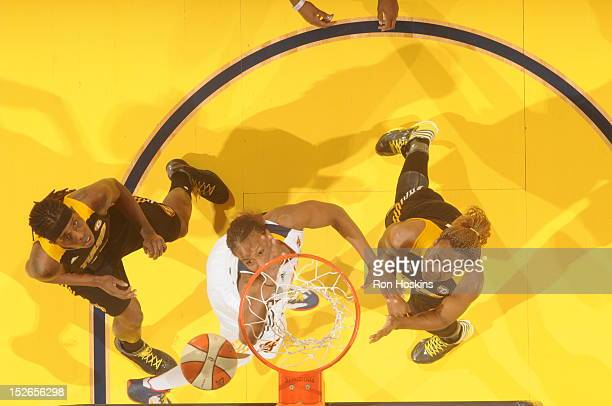 Tamika Catchings of the Indiana Fever battles Amber Holt and Roneeka Hodges of the Tulsa Shock for a rebound at Banker's Life Fieldhouse on September...