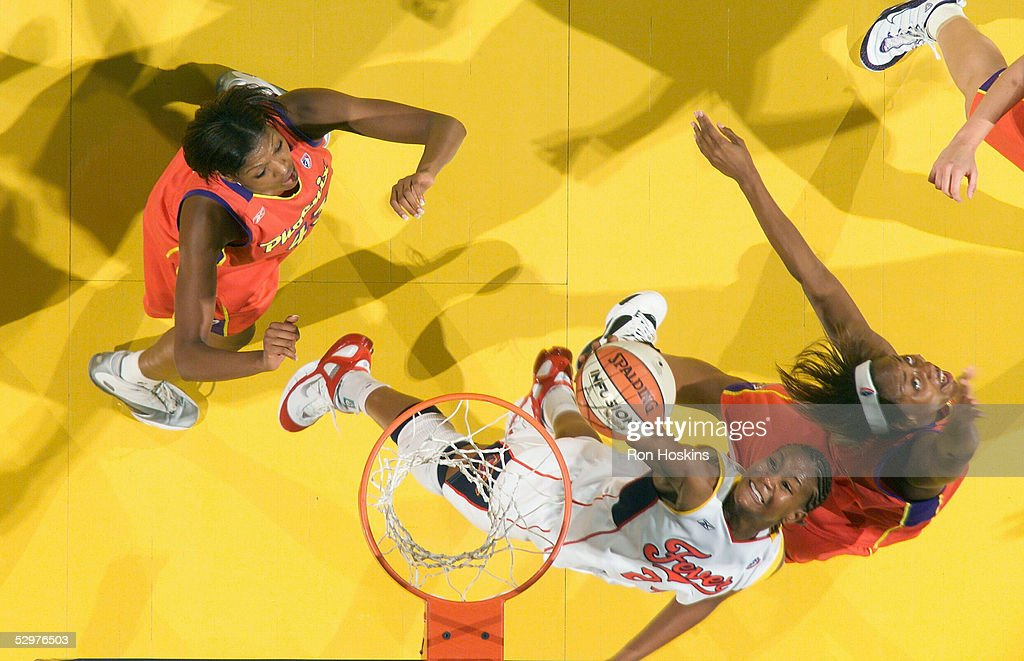Tamika Catchings of the Indiana Fever battles Angelina Williams and Ashley Robinson of the Phoenix Mercury on May 24 2005 at Conseco Fieldhouse in...