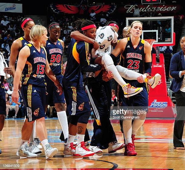 Tamika Catchings of the Indiana Fever is carried off the floor by Shavonte Zellous and Katie Douglas after an injury against the Atlanta Dream in...