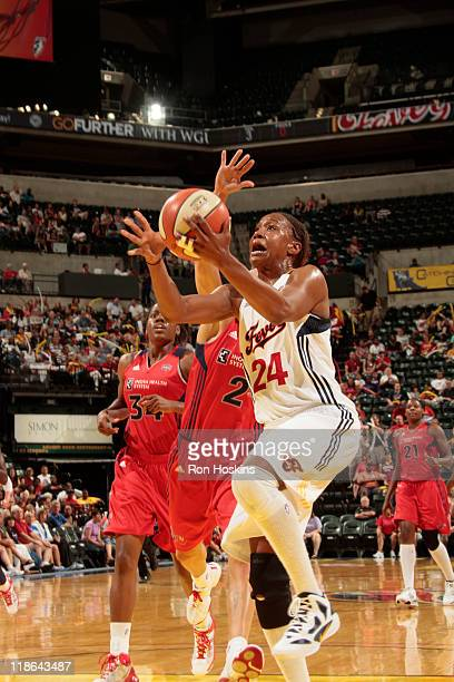 Tamika Catchings of the Indiana Fever lays the ball up on Kelly Miller of the Washington Mystics at Conseco Fieldhouse on July 9 2011 in Indianapolis...
