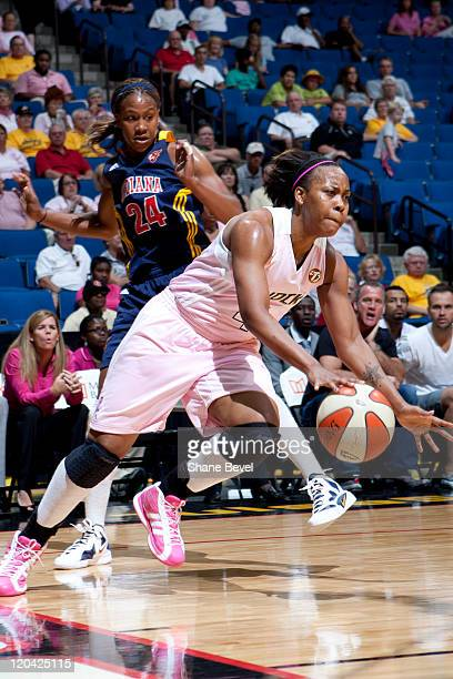Tamika Catchings of the Indiana Fever watches as Amber Holt of the Tulsa Shock drives to the hoop during the WNBA game on August 5 2011 at the BOK...