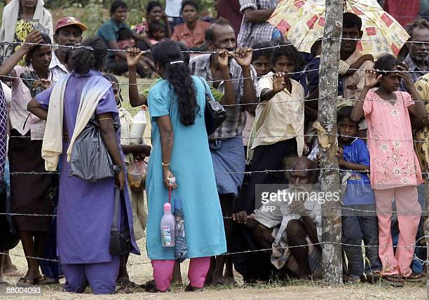 Tamil civilians stand behind a barbedwire fence in the Manik Farm refugee camp located on the outskirts of the northern Sri Lankan town of Vavuniya...
