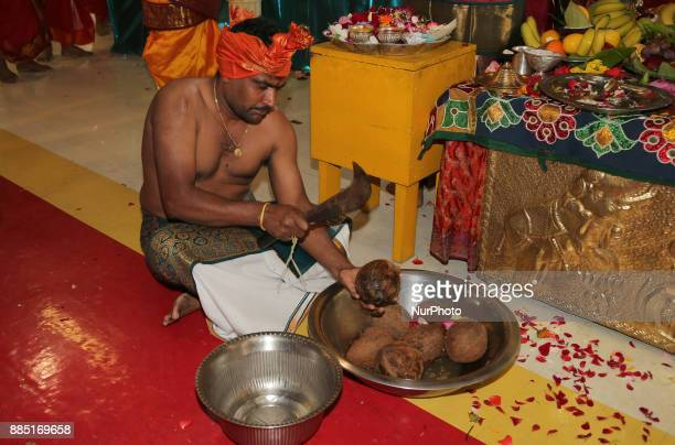 Tamil Hindu devotee breaks a coconut as part of special prayers during the Mahotsava Festival at a Hindu temple in Ontario Canada