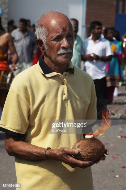 Tamil Hindu devotee carrying a flaming coconut during the Mahotsava Festival at a Hindu temple in Ontario Canada