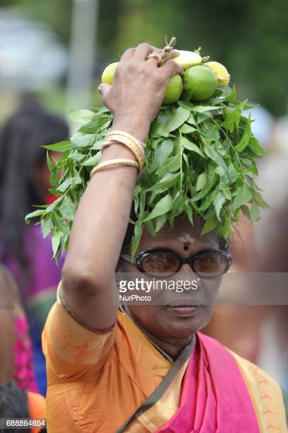 Tamil Hindu devotee carrying a pot of milk covered with limes and margosa leaves on her head during the Murugan Ther Festival at a Tamil Hindu temple...