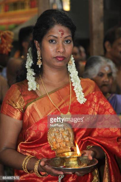 Tamil Hindu devotee holds a lamp during the Mahotsava Festival at a Hindu temple in Ontario Canada