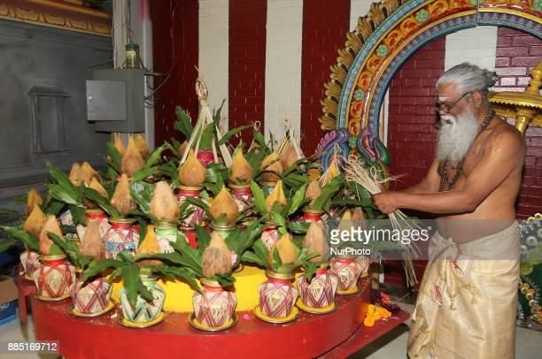 Tamil Hindu devotee preparing kalash for special prayers during the Mahotsava Festival at a Hindu temple in Ontario Canada
