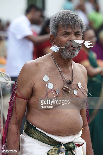Tamil Hindu devotee with body piercings and facial skewers as an act of penance during the Murugan Ther Festival at a Tamil Hindu temple in Ontario...