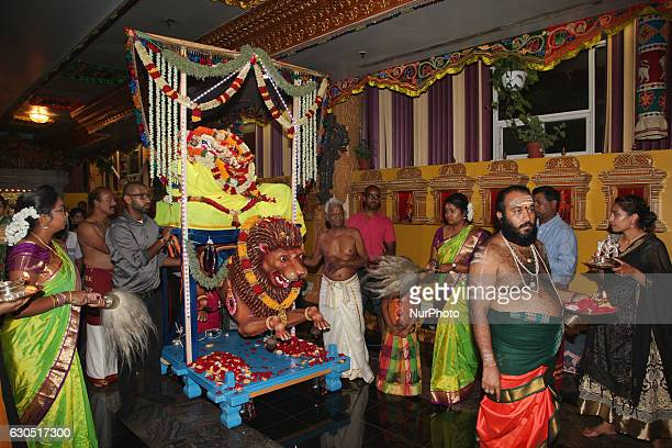 Tamil Hindu devotees escort the idol of the Goddess Durka as it makes its way around the temple during the Valvettithurai Athivairawar Festival in...