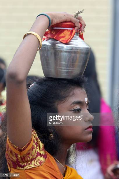 Tamil Hindu girl carrying a metal pot containing milk atop her head during the Vinayagar Ther Thiruvizha Festival in Ontario Canada This festival is...