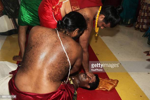 Tamil Hindu priest attend to a devotee who has collapsed after becoming entranced during the Mahotsava Festival at a Hindu temple in Ontario Canada