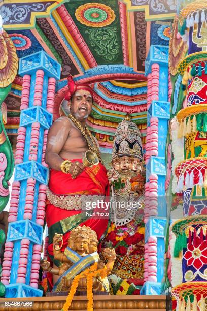 Tamil Hindu priest performs special prayers while riding in the chariot with the idol of Lord Murugan during the Mahotsava Festival at a Hindu temple...