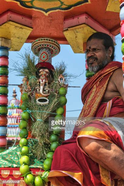 Tamil Hindu priest rides in the chariot with the idol of Lord Ganesh during a religious procession celebrating the Mahotsava Festival at a Hindu...