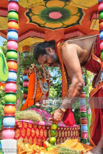 Tamil Hindu priest stands in the chariot while he adorns the idol of Lord Ganesh in green during the Mahotsava Festival at a Hindu temple in Ontario...