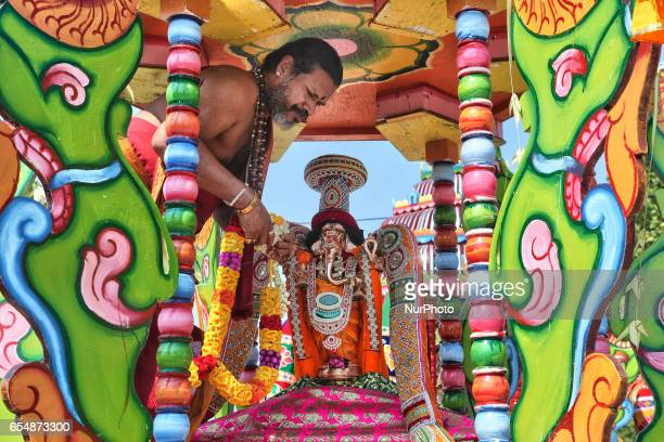 Tamil Hindu priest stands in the chariot while he prepares to adorn the idol of Lord Ganesh in green during the Mahotsava Festival at a Hindu temple...