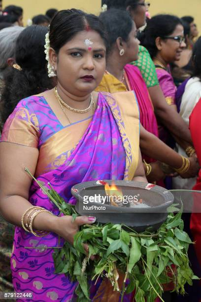 Tamil Hindu woman holds a clay pot with burning camphor atop margosa leaves during the Vinayagar Ther Thiruvizha Festival in Ontario Canada This...
