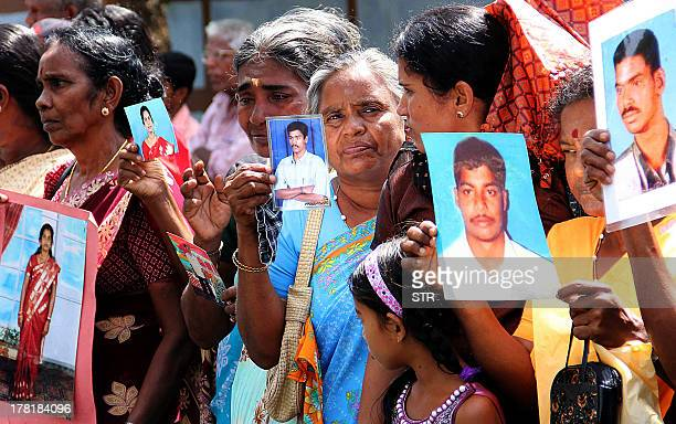 Tamil protesters hold photographs of missing relatives at a demonstration in the northern Sri Lankan town of Jaffna on August 27 2013 as UN Human...