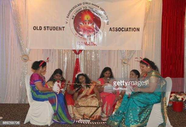 Tamil women singing Christmas songs while hitting a string with jingle bells during the V Rambaikulam Girls Maha Vidyalayam Old Students Association...