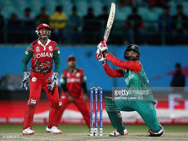 Tamim Iqbal of Bangladesh hits a six as Sultan Ahmed Captain of Oman looks on during the ICC World Twenty20 India 2016 match between Bangladesh and...