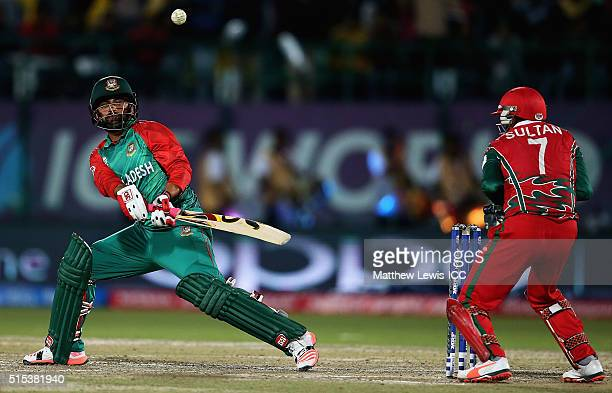 Tamim Iqbal of Bangladesh sweeps the ball towards the boundary as Sultan Ahmed Captain of Oman looks on during the ICC World Twenty20 India 2016...