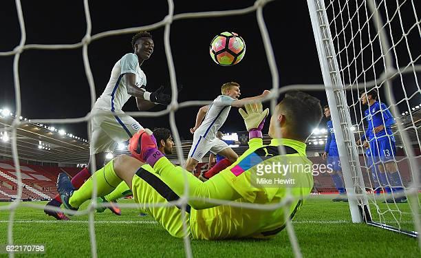 Tammy Abraham and Duncan Whatmore of England celebrate team mate Jack Steven's winning goal as goalkeeper Pierluigi Gollini of Italy retrieves the...