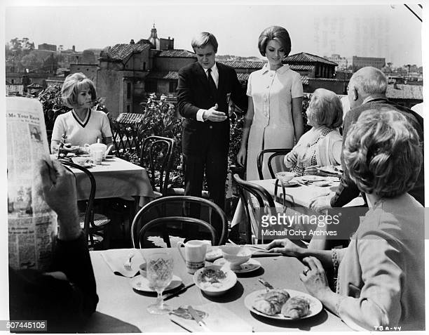 Tammy Grimes looks on as David McCallum introduces his girlfriend Sylva Koscina in a scene from the MGM movie 'Three Bites of the Apple' circa 1967