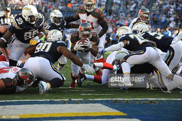 Tampa Bay Buccaneers Running Back Doug Martin dives between San Diego Chargers and San Diego Chargers Cornerback Craig Mager for a touchdown during...