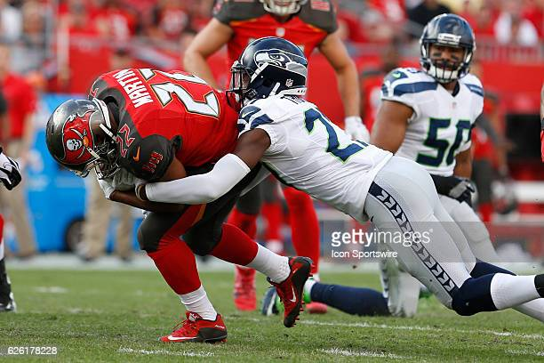 Tampa Bay Buccaneers running back Doug Martin is tackled by Seattle Seahawks defensive back Neiko Thorpe in the first quarter of the NFL game between...