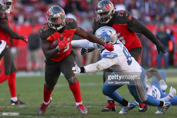 Tampa Bay Buccaneers running back Peyton Barber breaks a tackle from Detroit Lions defensive end Ezekiel Ansah in the 4th quarter of the NFL game...