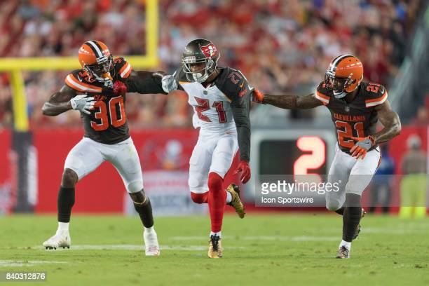 Tampa Bay Buccaneers safety Justin Evans tries to break through Cleveland Browns defensive back Derrick Kindred and Cleveland Browns defensive back...