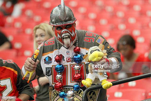 Tampa Bay Buccaneers super fan Keith 'Big Nasty' Kunzig chokes a chicken and a Falcons doll before the Tampa Bay Buccaneers defeated the Atlanta...
