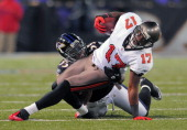 Tampa Bay Buccaneers wide receiver Arrelious Benn is pulled down by Baltimore Ravens linebacker Terrell Suggs after making a first down reception The...