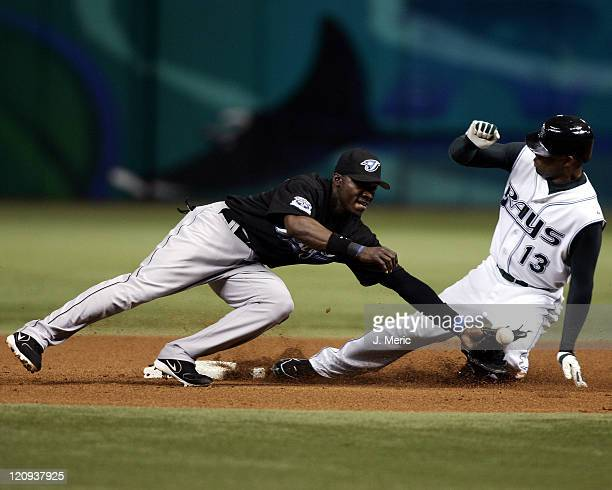 Tampa Bay Devil Rays outfielder Carl Crawford slides safely into second base with a steal as Toronto Blue Jays second baseman Orlando Hudson tries to...
