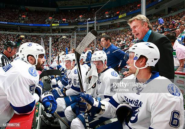 Tampa Bay Lightning assistant coach Rick Bowness talks to Jason Garrison during their NHL game against theVancouver Canucks at Rogers Arena October...