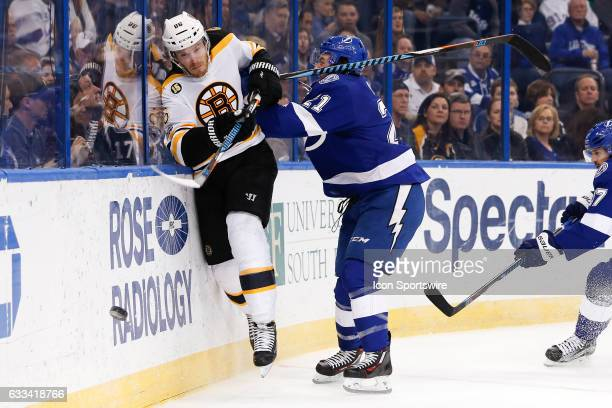 Tampa Bay Lightning center Brayden Point checks Boston Bruins defenseman Kevan Miller into the glass behind the Bruins net in the first period of the...