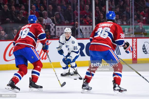 Tampa Bay Lightning Center Yanni Gourde controlling the puck facing Montreal Canadiens Defenceman Brandon Davidson and Montreal Canadiens Defenceman...