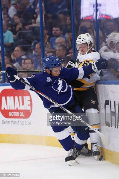 Tampa Bay Lightning defenseman Mikhail Sergachev checks Pittsburgh Penguins center Jake Guentzel in to the glass as they battle for the puck in the...