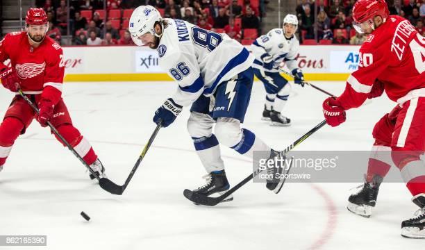 Tampa Bay Lightning forward Nikita Kucherov controls the puck between Detroit Red Wings forward Tomas Tatar and forward Henrik Zetterberg in the...