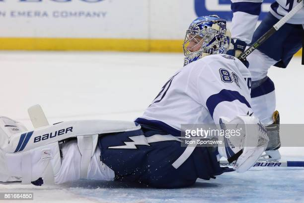 Tampa Bay Lightning goalie Andrei Vasilevskiy is able to block the puck with his glove as he falls to the ice in the 1st period of the NHL game...