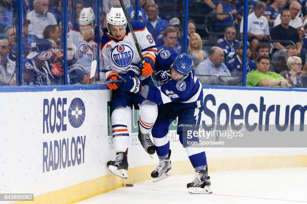 Tampa Bay Lightning left wing Ondrej Palat checks Edmonton Oilers defenseman Matt Benning into the glass behind the Oilers net in the first period of...
